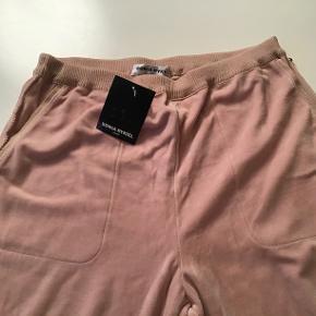 Nye lækre rosa velourbukser, hyggebukser. Livv. 80-90 cm. Skridtlængden 73 cm. Lommer i siderne. Bomuld, viscose, polyamid. Vige ben. Meget lækre.