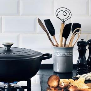 Skøn krukke fra Le Creuset  Højde ca 15 cm, diameter ca 12 cm  En bestik- og redskabskrukke fra Le Creuset er fremstillet i stentøj i alle de velkendte Le Creuset-farver. Bestik- og redskabskrukken er ideel til opbevaring af køkkenredskaber så som piskeris, madpincetter, palletter, grydeskeer etc. og kan samtidig fungere som et dekorativt og farverigt element på køkken- eller spisebordet; alternativt med bestik eller friske krydderurter.