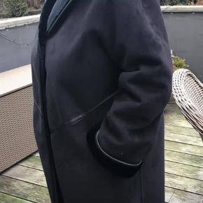 """Varetype: Frakke Farve: Sort  Lækker """"rulam"""" i sort """"fake"""" pels. Virkelig lækker udgave dom ligner og føles fuldstændigt som ægte rulam, super kvalitet!  Købt for kr. 3.000, men aldrig rigtig kommet i brug, så alene været på til pænt brug et par gange, og nu som det ses på billedet lidt for stor.  Størrelsen er angivet til 40,  men anslår den kan bruges også til en størrelse 42-44, alt efter hvor løst man ønsker den skal være.  Den har INGEN brugsspor overhovedet. Smid et bud, tænker start på kr. 1.000  pp."""