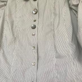 Tynde grå striber og forskellige knapper. 64%cotton, 31 polyamid, 5 elastan = meget stræk. Længde 63 cm. Str er 44, men passer måske bedst en str 42.