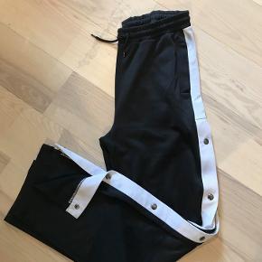Track pants fra BDG (urban outfitters), de har været brugt få gange. Sælges for kr. 100.-   Nypris 350,-  Porto 38 kr.  Kontakt mig også på 20867272. Se også min facebook gruppe Deal2deal vintage Mindre