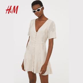 Sommerkjole, H&M Trend, str. S, Beige, Viscose, Ubrugt  Kort kjole i let, jacquardvævet kvalitet med V-udskæring og korte pufærmer. Kjolen lukkes foran med beklædte knapper og er skåret i taljen med let vidde i underdelen. Med for. Meget yndig og feminin kjole. Helt ny og ubrugt med mærkeseddel. Materiale: 75% viscose og 25% polyester. For: 100% viscose. Nypris: 449 Eventuel fragt lægges oveni: 38 til nærmeste posthus/butik Har kjolen i str. 36, 38 og 44. Alle helt nye og ubrugte med mærkesedler