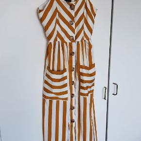 Karrygul/hvidstribet kjole af mærket QED London, købt på asos. Kjolen er vasket en enkelt gang, men er aldrig blevet brugt, da jeg desværre ikke kan passe den.  Normal i størrelsen. Går til lige over knæene. Smock i ryggen og justerbare stropper.  Fra dyre- og røgfrit hjem.