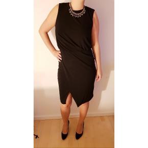 Kun brugt meget få gange. Passede ikke til min figur.  Elegant knælang sort kjole fra Mango i str xl / 42 .  Både til kontor eller fest.  Har dyb ryg.  Note: jeg er 180 cm i forhold til længden af kjolen på mig på billedet.