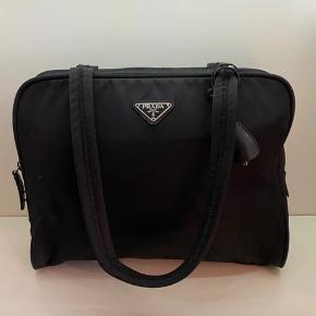 Prada håndtaske i sort nylon   Virklig pæn stand dog hsr den en lille limning indeni, intet man ser eller påvirker funktionen af tasken  32*27*10 cm   1795,- inkl moms