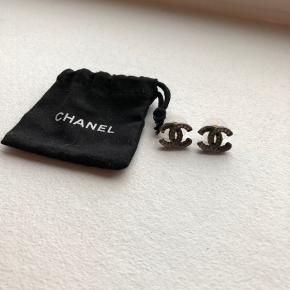 Sælger disse smukke og alt-anvendelige Chanel øreringe. Kombination af sølv - samt sorte sten - øreringene har dog mistet enkelte sten, men det er intet, som tydes, når de er i brug. Det ene stempel er faldet af den ene ørering. Dustbag medfølger ved køb - kvittering haves ikke længere, men de er købt for fire år siden i Chanel i Rom til 3600kr.  Pris: 1250kr.