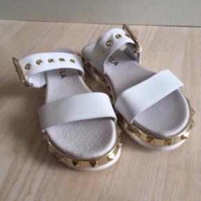 Fri porto i efterårsferien 🍁   Fede hvide skind sandaler / slippers fra Bukela. Str. 37. Med guld detaljer og spænde. Næsten som ny. Kan justeres over vristen. Nypris 900,-