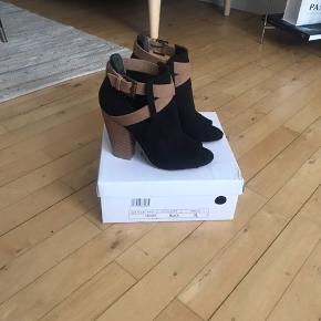 Sandaler i str. 36. Højde 12 cm. Med spænder som lukning. Ret behagelige at gå i selvom der ikke er plateu i.