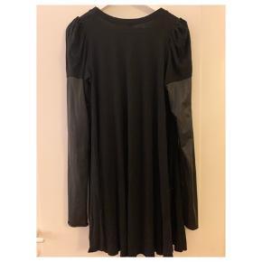 Super fed kjole der sidder til, med læderlook/shine ærmer og stræk i stoffet:)   Kommer fra røgfrit og dyrefrit hjem