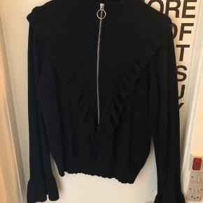 Flot sort sweater bluse med sølv lynlås foran og med detaljer ved ærmerne. Den fnuller meget lidt, men er ellers i god stand.