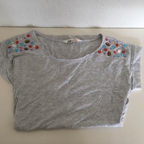 "T-shirt lysegrå yderst fin stand med de fedeste "" diamant sten ""  på skuldrene Sender gerne"
