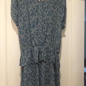 Kjolen er lidt kort, men går til midt på låret, kan også bruges som en bluse til et par bukser. Lækkert stof til varme dage