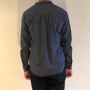Brugt få gange. Super fin skjorte med hvidt mønster, og lyserøde syninger omkring knapperne. Knappelukning ved ærmet