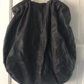 Stor rummelig lædertaske. Kan snøres til i toppen. To små åbne rum samt et lynlås rum inde i tasken.  Måler: 50 x 50 x 25 cm.  Aldrig brugt.