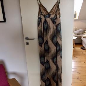 Super flot, lang sommerkjole med print af påfuglefjer. Elastik under brystet sikrer, at kjolen falder pænt. Stroppernes længde kan justeres efter behov.