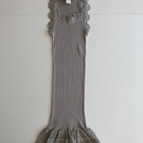 70% silke Den er ca. 81 cm målt fra nakken og ned.