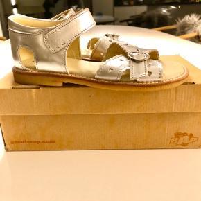 Helt nye læder sandaler i sølv. Aldrig brugt, da min datter er vokset ud af dem inden. De har velcro lukning, så er super lette for den lille pige hurtigt selv at få dem af og på.