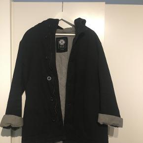 Super fed sort frakke med hætte fra det australske mærke Arvust. Det er en størrelse medium, men i virkeligheden sidder den som en størrelse large. Stadig i rigtig fin stand! Nypris 850,-