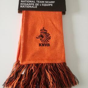 """Hermed sælges et helt nyt officielt Nederland/Holland tørklæde.  Farven er orange og lavet af Nike  Kommer med teksten """"Nederland"""", Nike logo og det officielle logo fra KNVB, som er det hollandske fodboldsforbunds logo.  Fast pris 30,-  Kan afhentes i Hvidovre efter aftale.  Kan også sendes med tracking for 38,-"""
