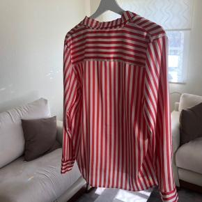 En meget fin og klassisk skjorte. Skjorten er mønstret med streger ned lodret i farverne hvid og rød.  Den er kun blevet brugt en enkel gang. Som vist på sidste billede er der en lille sort plet af brug efter maling, jeg har personligt ikke prøvet at fjerne det, men jeg tror sagtens at man kan.  - Prisen kan altid forhandles😊