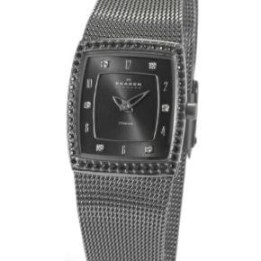 Skagen damearmbåndsur model Titanium med rektangulær urkasse, omkranset med sorte, facetslebne sten, sort skive med arabertal og similibesatte punktindikationer. Quartsværk. Flettet flexlænke med sikkerhedslukke. Urkasse 25 x 22 mm.  Giv et bud