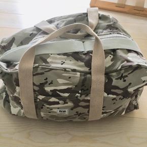 Fed weekend-taske fra Wood Wood. Måler 55x30x25 cm.  Har en lille lomme indvendig og en lomme i hver ende, der lukkes med trykknap.   Kom med et bud