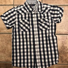 Kortærmet Skjorte fra Cottonfield i str. 10 år. Ternet i blå og hvid  Super fed ternet skjorte med korte ærmer og rød stjerne på den ene knap. Meget fin stand.  #30dayssellout 50 kr pp