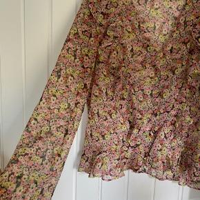 Super smuk blomstret bluse i gennemsigtigt stof 😍 virkelig perfekt skjorte i sort med gule, lyserøde og røde blomster. Den er så fin med flæser foran 👌🏼   Bemærk - afhentes i 8210 eller sendes med dao. Bytter ikke 🌸  ♻️ Bluse skjorte blomster blomstret rød lyserød gul