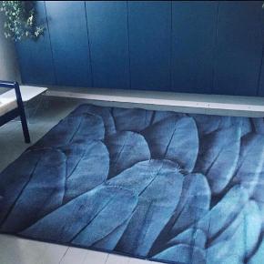 Rigtig lækkert unika gulvtæppe kun brugt i et par måneder i hjem uden røg og dyr.   Tæppet er specielt design og findes kun i 2 eksemplarer.   Det er fra Egetæpper og måler 2 x 2 meter. Blå med fjer.   Nypris 4500 kr.