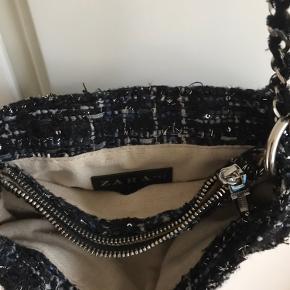 Fin lille skuldertaske fra Zara i tweedstof med glittertråd. Dobbelt kæde. Tre rum hvoraf et med lynlås.
