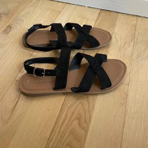 Fine og enkle sandaler med sort ruskind. Kan spændes, da der er flere huller i remmen.  Størrelse 39. Fra mærket New Look.  Har kun været brugt 1 gang og fremstår derfor stadig som næsten nye.  Mængderabat gives ved køb af flere dele. Sender gerne på købers regning.