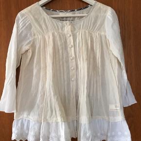 Fin skjorte i størrelse 0, men vil også kunne passe en str. S. Et mix med hvide ærmer og en hvid blonde forneden. Og så en krop af lys beige/naturhvid. Flot til et par cowboybukser.