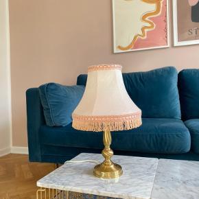 Retro vintage lyserød  messinglampe med lys lyserød lampeskærm med frynser.   37,5 cm i højden  Lampeskærm: 22 cm i diameter  Lampefod 10 cm i diamter   Meget velholdt. Kan både sendes eller afhentes i Aarhus c :)  Frynselampe