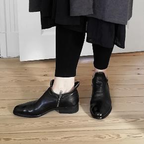 Bytter ikke. Eksklusiv porto. Super lækre håndsyede støvler fra Italien. Super kvalitet. Fantastisk gode pasform. Støvler fra Officine Creative, håndsyede fra Italien. Støvlerne er store i størrelsen. Støvlerne er en Str. 38, men jeg har skrevet str. 38,5, da støvlerne er store i størrelsen.  Udvendige mål 27,5 cm. Indvendige fra snudespids til hæl ca. 26 cm, (svært at måle). Der er lynlås i begge sider, indvendig og udvendig. Farve som billederne, sort. Der er lynlås i begge sider. Støvlerne er nye. Har aldrig været gået med, blot stået i mit skab.