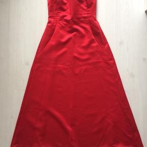 Fantastisk flot stropløs galla-kjole i rødt satin-look.  Lukkes med lynlås i venstre side.  Flot detalje med satin-bånd på ryggen.  Rødt sjal med pailletter medfølger.  Modellen på billedet er 165 cm.  Længden er 119 cm, brystmålet er 80 cm, og taljen er 74 cm.