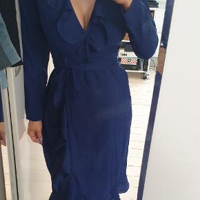 Smuk blå kjole med flæser der er åbent ved ryggen  Str 36  det er en slå om kjole  jeg er 171cm høj  den er brugt en gang, fremstår flot og næsten som ny   den sælges for 265kr eller 300kr inkl fragt med DAO