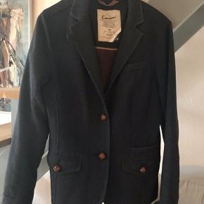 LÆKKER uldblazer fra Marc O'Polos hippe mærke Campus. Købt i Berlin og brugt ganske lidt. Blazeren har masse af skønne detaljer og lækkert foer. Brystmål 46 cm, længde 66 cm og ærmelængde 63 cm.