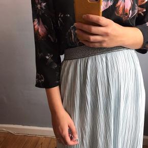 Blå skinnende lang nederdel med sølv elastik i livet. Jeg har 1,65 og sætter den ved navlen.  Afhentes i Sydhavnen eller sendes via DAO  Blusen er også til salg