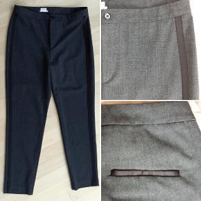 Smukke bukser i koksgrå med sort galoner, lidt i smoking stil. Model hedder Fiona Peg.  Størrelse svarer til en 38, og er 7/8 i længden.