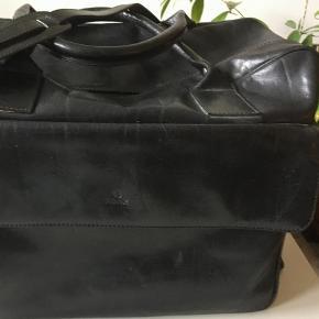 Varetype: Rejsetaske Størrelse: 405x20x32 Farve: Sort Oprindelig købspris: 2000 kr.  Rejsetaske i sort skind fra Adax. Der er en stor lomme foran og en lynlåslomme indeni. To håndtag og lang skulderrem der kan reguleres.  Tasken måler 45x20x32. Nypris var 2000kr og tasken er kun brugt få gange. Pris 600kr. Sælger betaler evt porto.