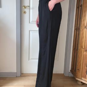 Smukke, sorte, højtaljede og løse bukser med elastik i taljen samt lommer Lækker satin kvalitet, der er perfekt til sommer Brugt en enkelt gang i få timer #secondchancesummer
