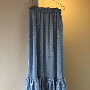 High waist midi-nederdel som nederst har en flæsekant. Derudover så har nederdelen elastik i taljen.   Farve - Lyseblå med hvide prikker  Str. M/medium  Maskinvask - 30 grader  Materiale - 100% polyester