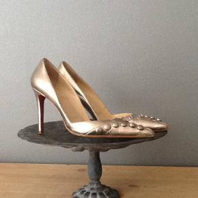 Stiletter i guld og med knapper fra Christian Louboutin og med de klassiske røde såler. Brugte, men kan godt bruges til en julefrokost eller anden festlig lejlighed eller to. Prisen er sat derefter.