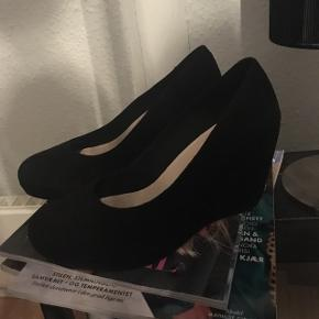 Så lækre, klassiske sorte Vagabond kilehæl sandaler/sko i ruskind i str 40, super behagelig højde og model. 😊  Kun prøvet på indenfor et par gange, så standen er fuldkommen som ny, hvilket også kan ses på billederne. 😉  Jeg tror jeg har haft gemt æsken til kilehælene, og nyprisen lå på en 1.000-1.100 kr. ca.   Hvis de skal sendes, betaler køber fragt.  Mvh Betina Thy