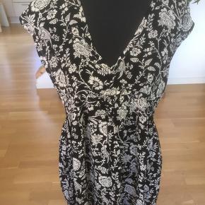 Fin lang tunika i ren viscose. Sort med hvidt blomster print. Side lommer.