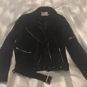 Den lækreste jakke fra Minimum med biker design og i imiteret ruskind, der er så blødt og behageligt. Jakken har fedt langt aftageligt bælte med sølvspænde. :)  Jakken er aldrig nogensinde brugt og jeg har købt den for ca. 1,5 år siden på Magasin's webshop til 1.100 kr. Det er som sagt en str. 38/M. Dog, alt afhængig af hvilket look man ønsker, vil jeg mene at jakken godt kan passes af flere størrelser, hvis man fx er mindre end en M/38, vil der jo så måske kunne være en tykkere bluse/sweater indenunder og man vil få et mere oversized, cool udtryk. 😉  Jakken har seje lynlås detalje på den ene arm og bærer alt i alt præg af den høje kvalitet som Minimum altid tilbyder når det kommer til deres kollektioner.   Hvis den skal sendes, betaler køber fragt.   Hilsen Betina Thy