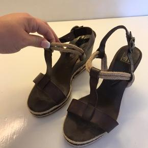 Kilehæl sandaler i brunt læder og tekstil str. 39. Behagelige at have på, men får dem bare ikke brugt.