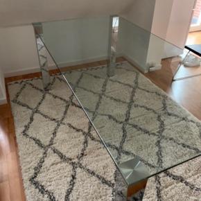 Kante spisebord i glas med sølvben. Mål: 75x180x90 cm. Bud modtages. Har lette brugstegn. Afhentes.
