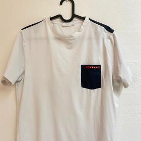 Prada t-shirt med lomme samt detalje på begge skulder.   Trøjen er godt vedligeholdt i står i en cond 8.5-9/10  Stil gerne spørgsmål eller byd i chat