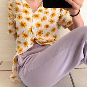 Flotteste blomster solsikke skjorte/tshirt. Fra ukendt mærke, i rigtig flot stand. Skjorten er en smule lang i det, og er et par cm længere bagpå end foran.  Giver et fedt vintage / retro look. Bud er meget velkomne